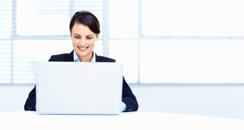Portrait of a cute smiling business woman working on a laptop with copyspace